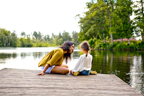 Mother and daughter on pier beside lake in Friseboda, Swedenの写真素材 [FYI02210141]