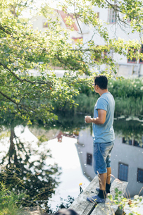 Mid adult man standing next to a river in Mortfors, Swedenの写真素材 [FYI02210144]