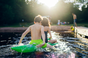 Brother and sister on a pool toy in a lake in Kappemalagol, Swedenの写真素材 [FYI02210149]