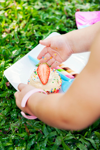 Girl´s hands touching cupcake at birthday picnicの写真素材 [FYI02210177]
