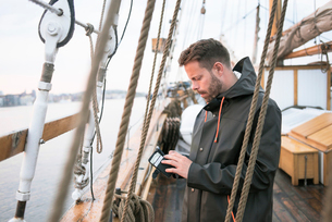 Sweden, Vastra Gotaland, Gothenburg, Man checking wallet on sailboatの写真素材 [FYI02210210]