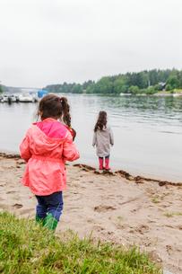 Sweden, Uppland, Roslagen, Vato, Two girls (4-5, 6-7) standing by lake shoreの写真素材 [FYI02210236]