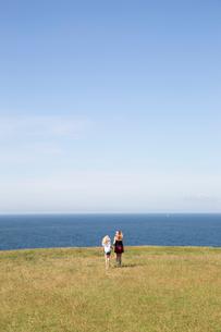 Sisters walking in a field next to the sea in Kaseberga, Swedenの写真素材 [FYI02210277]