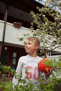 Finland, Uusimaa, Boy (6-7) holding ball in backyardの写真素材 [FYI02210301]