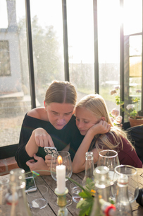 Sisters looking at a cell phone at a restaurant in Osterlen, Swedenの写真素材 [FYI02210336]