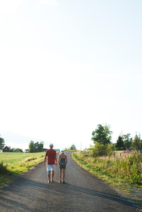 Father and daughter walking along rural road in Smaland, Swedenの写真素材 [FYI02210341]