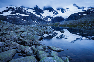 Norway, Jotunheimen, Sentraltind, Men camping in snowy mountain landscape with riverの写真素材 [FYI02210347]