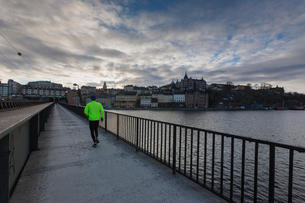 Man running along waterfront in Stockholm, Swedenの写真素材 [FYI02210350]