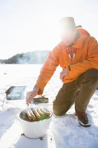 Man grilling sausages during winter in Akersberga, Swedenの写真素材 [FYI02210362]