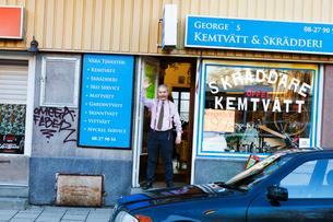 Man waving at door of storefrontの写真素材 [FYI02210369]