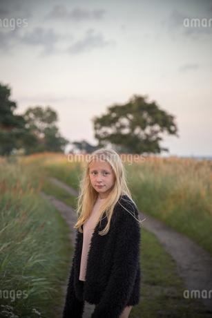 Girl standing in front of a unpaved road in Ornahusen, Swedenの写真素材 [FYI02210382]