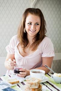 Young woman eating breakfastの写真素材 [FYI02210413]