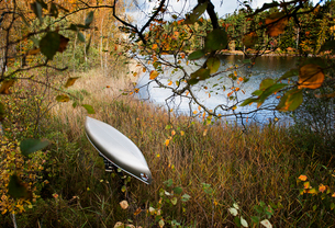 Sweden, Smaland, Mature man carrying boat through tall grass on lakeshore in autumn forestの写真素材 [FYI02210455]