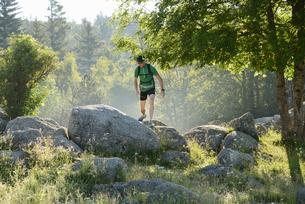 Man walking on rocks in the forest in Lozere, Franceの写真素材 [FYI02210456]