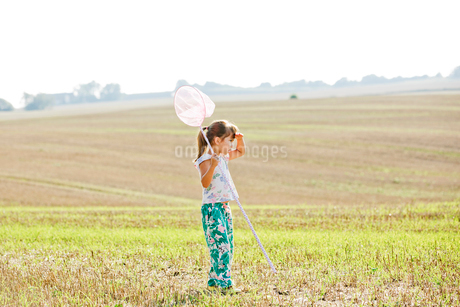 Girl with bug net in field in Friseboda, Swedenの写真素材 [FYI02210477]