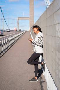 Sweden, Vastergotland, Gothenburg, Young woman listening music on smart phone on bridgeの写真素材 [FYI02210497]
