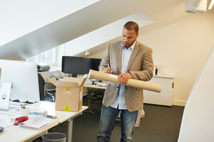 Sweden, Businessman writing note on paper tube in officeの写真素材 [FYI02210507]