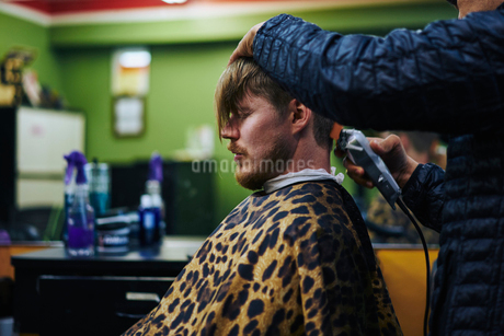 Man getting haircut in a barber in Americaの写真素材 [FYI02210513]