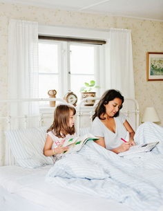 Mother and daughter reading in bedの写真素材 [FYI02210523]