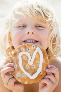 A young girl holding a pastry with heart shaped icingの写真素材 [FYI02210568]