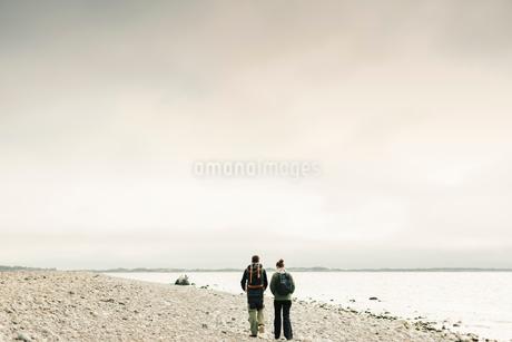 Rear view of couple walking along rocky coastline in Stockholm, Swedenの写真素材 [FYI02210576]