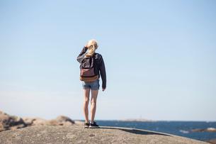 Girl standing on a rock overlooking the sea in Bohuslan, Swedenの写真素材 [FYI02210603]