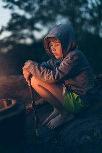 Boy sitting by campfire in Swedenの写真素材 [FYI02210625]