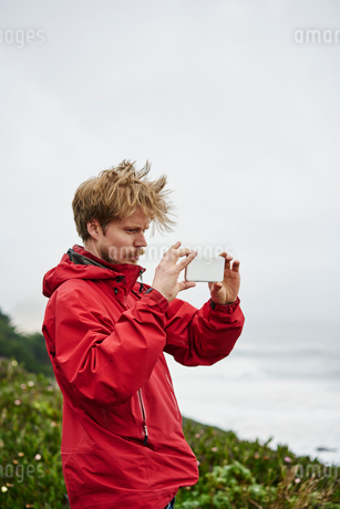 Man taking photograph at Big Sur in California, USAの写真素材 [FYI02210630]