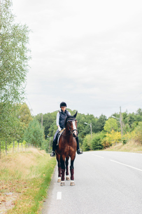 Sweden, Blekinge, Mid adult woman riding horse on road through forestの写真素材 [FYI02210633]