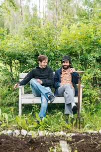 Friends sitting with a gardening fork next to a garden in Dalarna, Swedenの写真素材 [FYI02210638]