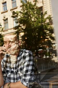 Sweden, Man sitting, talking on phoneの写真素材 [FYI02210644]