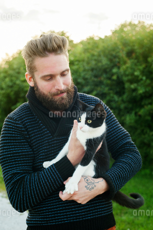 Young man holding a cat in Swedenの写真素材 [FYI02210648]