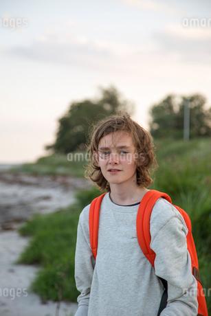 Teenage boy wearing a backpack on a beach in Osterlen, Swedenの写真素材 [FYI02210689]
