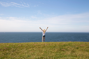 Girl with her arms raised in a field next to the sea in Kaseberga, Swedenの写真素材 [FYI02210695]