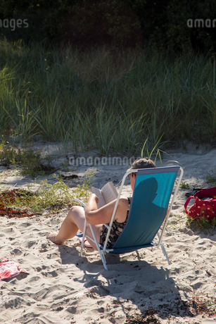 Mid adult woman reading on a beach in Osterlen, Swedenの写真素材 [FYI02210700]