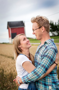 Finland, Uusimaa, Siuntio, Mid adult couple embracing in wheat fieldの写真素材 [FYI02210739]