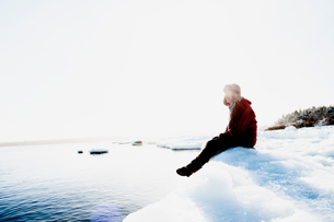 Man sitting on ice by sea in Biludden, Swedenの写真素材 [FYI02210741]