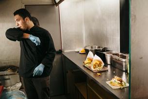 Chef preparing burgers in his food truckの写真素材 [FYI02210755]