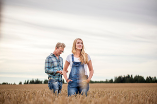 Finland, Uusimaa, Siuntio, Mid adult couple standing in wheat fieldの写真素材 [FYI02210775]