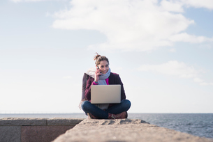 Sweden, Skane, Malmo, Woman sitting with computer against seaの写真素材 [FYI02210780]