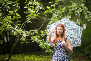 Finland, Pirkanmaa, Tampere, Woman wearing floral dress standing with umbrella in park and taking seの写真素材 [FYI02210795]