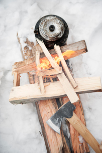 Sweden, Kettle and axe by campfire on snowの写真素材 [FYI02210797]