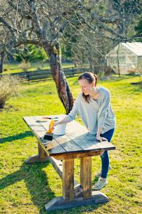 Finland, Paijat-Hame, Heinola, Mid adult woman oiling wooden table in gardenの写真素材 [FYI02210807]