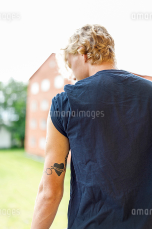 Rear view of young man with tattoo on arm in Finspang, Swedenの写真素材 [FYI02210878]