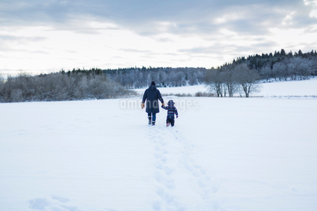 Rear view of mother and child walking in snowの写真素材 [FYI02210886]