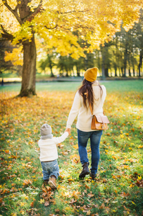 Rear view of mother and son in autumn leaves in Swedenの写真素材 [FYI02210888]