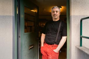 Portrait of craftsman in doorway of guitar making workshopの写真素材 [FYI02210901]