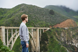 Man standing in front of bridge and mountains at Big Sur in California, USAの写真素材 [FYI02210909]