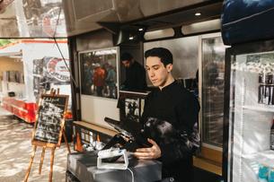 Food truck worker managing the cash registerの写真素材 [FYI02210938]