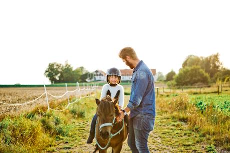 Man helping his daughter ride horse in Friseboda, Swedenの写真素材 [FYI02210966]